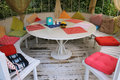 Summer pavilion with white round table and multicolored pillows.