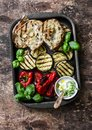 Summer picnic grilled vegetables - eggplant, bell peppers, ciabatta, yogurt sauce, basil in baking sheet on wooden background, top Royalty Free Stock Photo