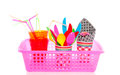 Summer picnic tools colorful plastic cutlery in plastic cups with a pink basket Stock Photo