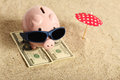 Summer piggy bank standing on towel from greenback hundred dollars with sunglasses on the beach and red parasol Royalty Free Stock Photo