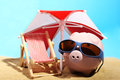 Summer piggy bank with sunglasses standing on sand under red and white sunshade next to beach chair Royalty Free Stock Photo