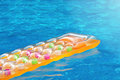 Summer pool dream multicolored inflatable matress floating in a blue swimming dreaming on days Stock Image