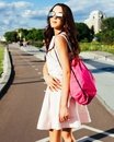 Summer portrait of an asian girl in a bright outfit and sunglasses with a pink backpack on the road. Los Angeles Royalty Free Stock Photo