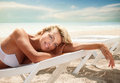 Summer portrait of beautiful tanned woman lying on sea beach Royalty Free Stock Photos