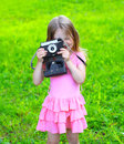 Summer portrait child with old retro vintage camera having fun outdoors on the grass Royalty Free Stock Photography