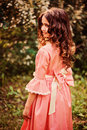 Summer portrait of curly smiling child girl in pink fairytale princess dress in the forest Royalty Free Stock Photo