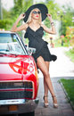 Summer portrait of stylish blonde vintage woman with long legs posing near red retro car. fashionable attractive fair hair female Royalty Free Stock Photo