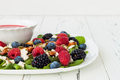 Summer refreshing spinach mixed berry salad with pumpkin and sunflower seeds, almonds, feta cheese and red raspberry vinaigrette Royalty Free Stock Photo