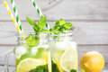 Summer refreshing water with cucumber, lemon, mint and ice in mason jar on a white wooden background. Rustic style. Royalty Free Stock Photo
