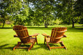 Summer relaxing two wooden adirondack chairs on lush green lawn with trees Royalty Free Stock Photos