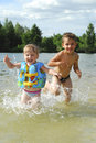 In summer the river indulge boy and girl they are catching up with each other sprinkles Royalty Free Stock Images