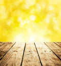 Summer rustic template background with wooden table and text space old vintage planked wood in perspective on bright yellow bokeh Royalty Free Stock Photo