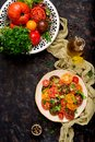 Summer salad of tomatoes of different colors with green herbs Royalty Free Stock Photo