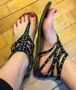 Summer sandals on woof floor pink painted toes in some black Stock Photos