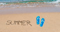 Summer and sandals writing blue flip flops on a golden shore Royalty Free Stock Images
