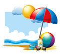 Summer scene with ball and umbrella on beach Royalty Free Stock Photo