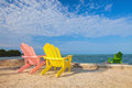 Summer scene with colorful lounge chairs on a tropical beach in florida blue sky and ocean in the background Stock Photography