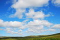 Summer sky above the green hills of mageroya white clouds float across blue mossy is photographed in Stock Photography