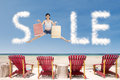 Summer special offer concept sale cloud with girl jumping over beach chairs Stock Photography