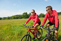 Summer - Sportive couple riding bike in meadow Stock Image