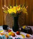 Summer Still Life With A Bouquet Of Yellow Lilies, Apricots And An Old Camera.