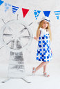 Summer style girl in fashion dress next to decorative wooden steer wheel Stock Images