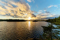 Summer sunset over the forest lake with clouds Stock Photo