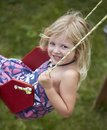 Summer swinging little girl on swing set and smiling at camera Royalty Free Stock Image