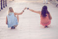 Summer teens girls sitting on skateboards vacation Royalty Free Stock Images