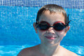 Summer time in the pool eight years old kid swimming looking with his goggles Stock Image