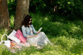 Summer time. Young woman at a picnic reading an e-book.