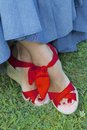 Summer toes close up of a woman s feet in pretty red shoes painted and draped with long denim skirt Royalty Free Stock Images