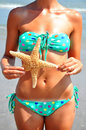 Summer travel fitness concept beautiful female body holding a starfish at the ocean Stock Photography