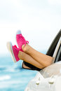 Summer vacation in car concept road trip woman legs out the windows on sea background female legs out of window for freedom travel Royalty Free Stock Photos