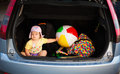 Summer vacation car luggage funny image with baby sitting in trunk full of going in Royalty Free Stock Image