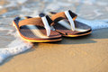 Summer vacation concept flip flops on a sandy ocean beach Stock Photo