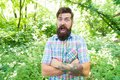 Summer vacation concept. United with environment. Man bearded hipster green trees background. Emotional nature lover Royalty Free Stock Photo