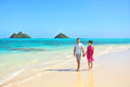 Summer vacation couple walking on hawaii beach landscape young adults relaxing together enjoying their holidays by pristine Royalty Free Stock Images