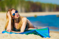 Summer vacation girl in bikini sunbathing on beach sexy tanning the young woman relaxing the sea coast summertime Royalty Free Stock Photo