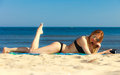 Summer vacation Girl with phone tanning on beach Royalty Free Stock Photo
