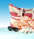 Summer vacation holiday gear with red and white strip beach bag, flip flop things, shell and sunglasses Royalty Free Stock Photo