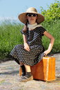 Summer vacation perky child girl in retro dress is sitting on a suitcase at the roadside Stock Photos