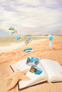 Summer vacation postcards flying from open book on the beach Stock Images
