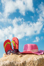 Summer vacation red flip flop sunglasses and floppy hat at the beach Royalty Free Stock Photo