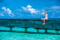 Summer vacation relaxation beautiful female sitting on wooden bridge woman enjoying peaceful beach landscape girl on tropical Stock Photography