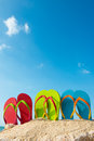 Summer vacation row of colorful flip flops on beach against sunny sky Stock Image