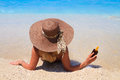 Summer vacation woman on beach the in straw hat holding a sun lotion bottle and looking at the ocean Royalty Free Stock Photos