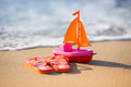 Summer vacations concept flip flops and toy sailing boat at the beach and travel Stock Photo