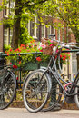 Summer view of bicycles in the dutch city amsterdam with flowers on a canal bridge Royalty Free Stock Image