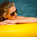 Summer woman lying on yellow floating mattress Royalty Free Stock Photos
